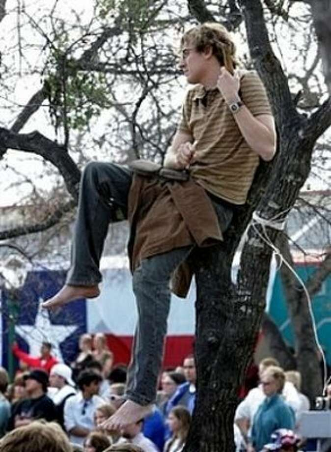 A supporter of Democratic presidential hopeful Sen. Barack Obama, D-Ill., watches from a tree during a town hall meeting in San Antonio, Tuesday, Feb. 19, 2008. (AP Photo/Eric Gay) (AP)