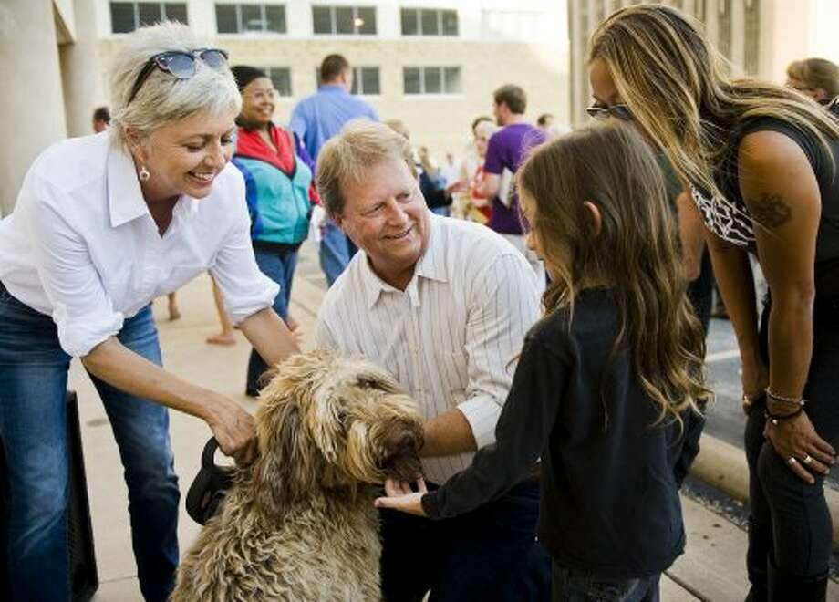 U.S. Senate candidate Paul Sadler (D), center, and his wife, Sherri, left, share a moment with their dog, Murphy, and young supporters during a fish fry at the American Federation of Labor - Congress of Industrial Organizations in Austin, TX on Fri., Aug. 31, 2012. (Ashley Landis / Houston Chronicle)