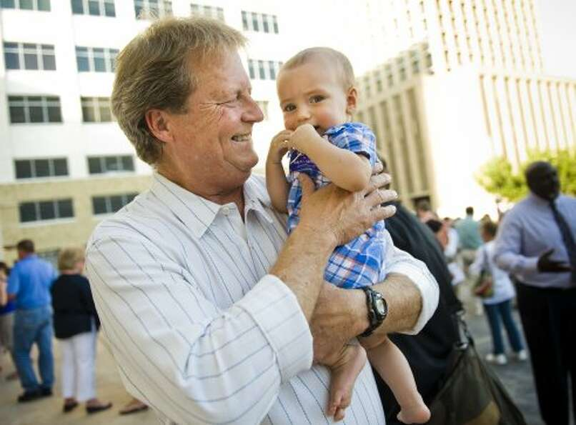 U.S. Senate candidate Paul Sadler (D) holds 10-month-old Pablo Hinojosa-Donisi, son of Austin ISD sc