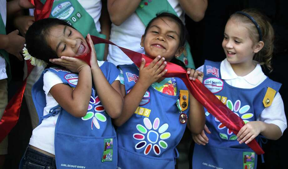 Oct. 2: Marah Flores (from left), Alysah Medina and Vickie Kent, all members of Girl Scout Daisy Troop 2509, play with the ribbon following the cutting at the grand opening of the new West Side Girl Scout Leadership Center at Coronado/Escobar. Photo: BOB OWEN, San Antonio Express-News / © 2012 San Antonio Express-News
