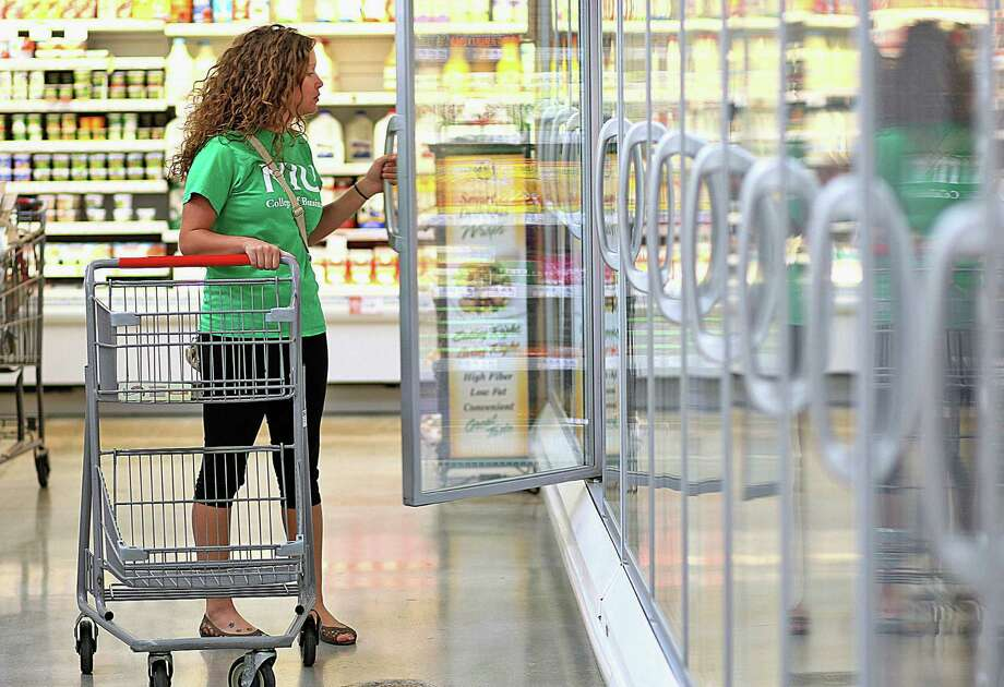 A young woman shops in a grocery store in Sycamore, Ill. Scott Burns says it is becoming more difficult for retirees to afford to buy food from their savings.  Photo: Kyle Bursaw / Daily Chronicle