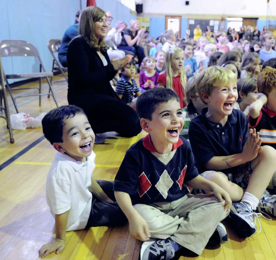 Old Greenwich School kindergartners, from left, Hayden Weaver, Alex Abrams and James Markline, all 5, react with smiles during the annual Pumpkin Lady's Unveiling that took place via a video feed in the gym due to rainy weather at the Old Greenwich School, Tuesday afternoon, Oct. 2, 2012. Photo: Bob Luckey / Greenwich Time