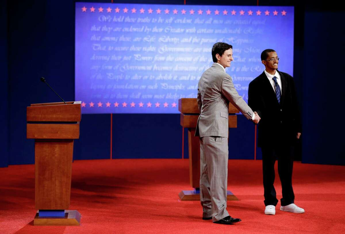 Stand-ins for Republican presidential candidate, former Massachusetts Gov. Mitt Romney, left, and President Barack Obama, shake hands on stage during a rehearsal for a debate at the University of Denver ,Tuesday, Oct. 2, 2012, in Denver. President Barack Obama and Republican presidential candidate and former Massachusetts Gov. Mitt Romney will hold their first debate Wednesday. (AP Photo/David Goldman)