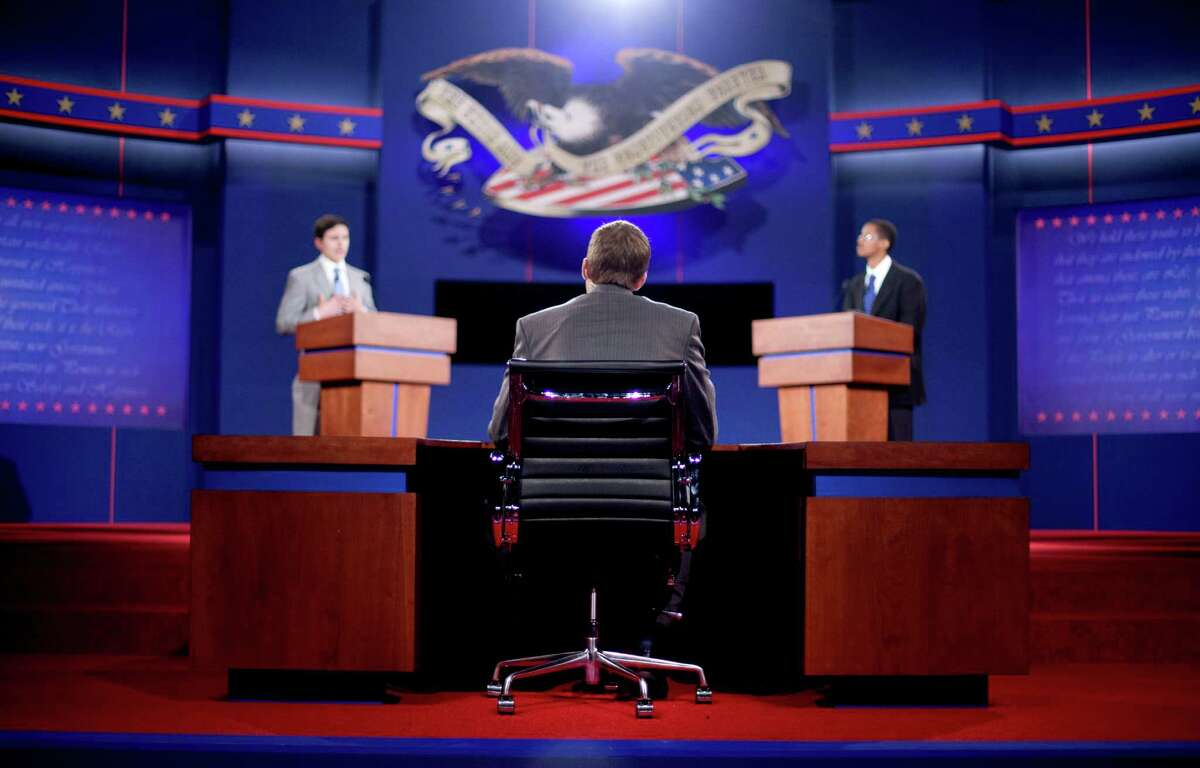 Stand-ins for moderator Jim Lehrer, center, Republican presidential candidate, former Massachusetts Gov. Mitt Romney, left, and President Barack Obama, right, run through a rehearsal for a debate at the University of Denver Tuesday, Oct. 2, 2012, in Denver. President Barack Obama and Republican presidential candidate and former Massachusetts Gov. Mitt Romney will hold their first debate Wednesday. (AP Photo/David Goldman)