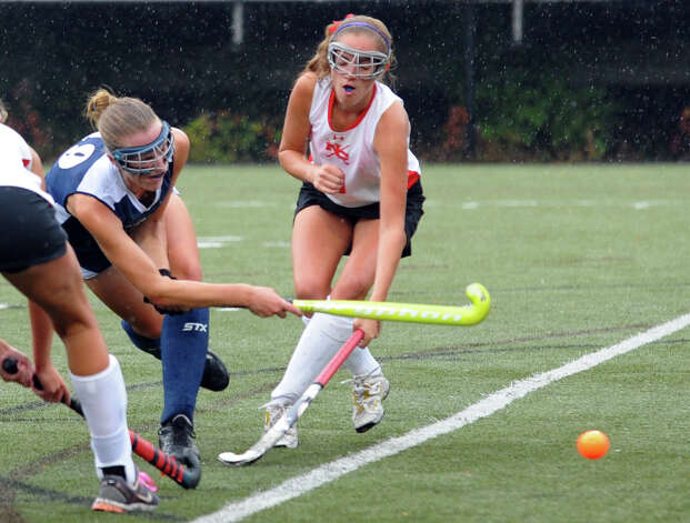 Staples #19 Elizabeth Bennewitz attempts a goal shot as New Canaan's #9 Bridget Falcone tries to block, during girls field hockey action in New Canaan, Conn. on Tuesday October 2, 2012. Photo: Christian Abraham / Connecticut Post