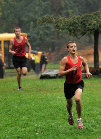 Pomperaug brothers Jason Oemcke, right, and Evan Oemcke finish first and second, respectively, during the cross country meet at Tarrywile Park in Danbury on Tuesday, Oct. 2, 2012. Photo: Jason Rearick / The News-Times