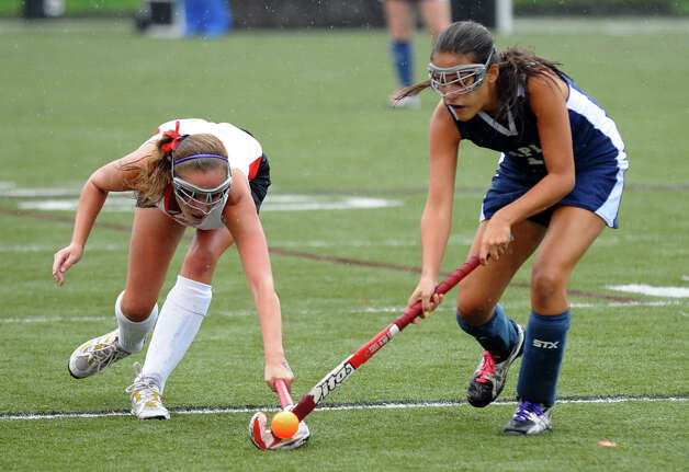 New Canaan's #9 Bridget Falcone tries to intercept the ball from Staples #12 Audrey Reedy, during girls field hockey action in New Canaan, Conn. on Tuesday October 2, 2012. Photo: Christian Abraham / Connecticut Post