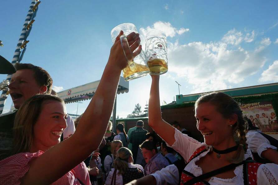 Revellers enjoy themselves as they drink beer outside the Braeurosl beer tent during day 7 of Oktobe