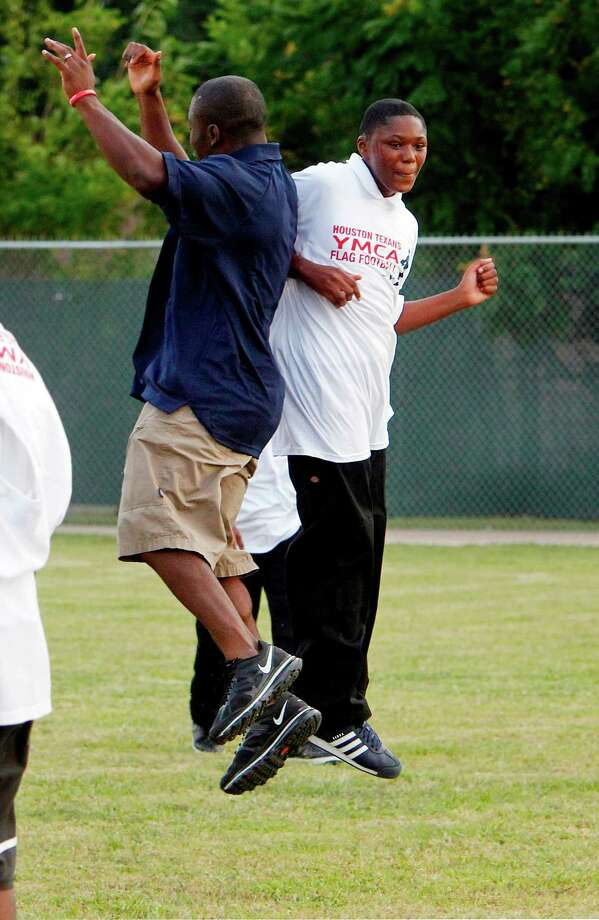 Houston Texans RB Justin Forsett celebrates with Denzell Jack, 12, after a drill during practice at the Houston Texans YMCA on Tuesday, Oct. 2, 2012, in Houston. Photo: Mayra Beltran, Houston Chronicle / © 2012 Houston Chronicle