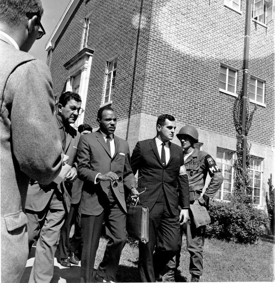 FILE - In a  Oct. 2, 1962 file photo, James Meredith, center with briefcase, is escorted to the University of Mississippi campus in Oxford. Escorting Meredith is Chief U.S. Marshal James McShane, left, and an unidentified marshal at right. Meredith, the first black student to attend the University of Mississippi after integration, says he doesn't plan to participate in the university's commemoration of his history-making enrollment 50 years ago, which prompted a state-federal standoff, sparked deadly mob violence and ultimately ended the university's official policy of racial segregation.  (AP Photo, File) / AP