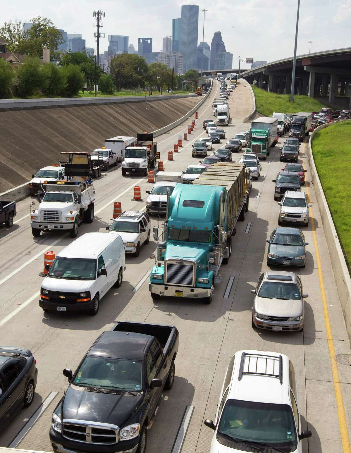 Traffic backs up Tuesday as an 18-wheeler wreck blocks lanes on Interstate 10 eastbound near U.S. 59. A report says Houston drivers spend hundreds of dollars extra each year because of accidents and congestion, which wastes time and fuel.