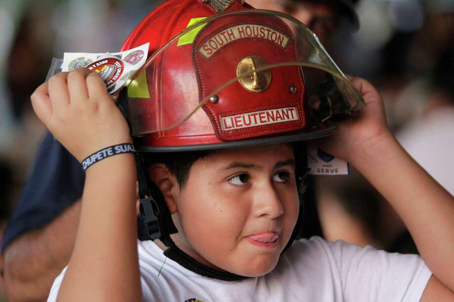Joshua Martinez, 10, tries on the helmet of South Houston Fire Dept. Lt. Robert Kyle during National Night Out at Ave. A Park Tuesday, Oct. 2, 2012, in South Houston. Photo: Melissa Phillip, Houston Chronicle / © 2012 Houston Chronicle