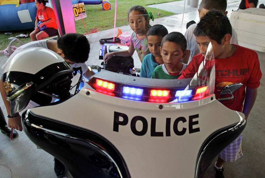 A group of kids look at a South Houston Police Dept. motorcycle during National Night Out at Ave. A Park Tuesday, Oct. 2, 2012, in South Houston. Photo: Melissa Phillip, Houston Chronicle / © 2012 Houston Chronicle