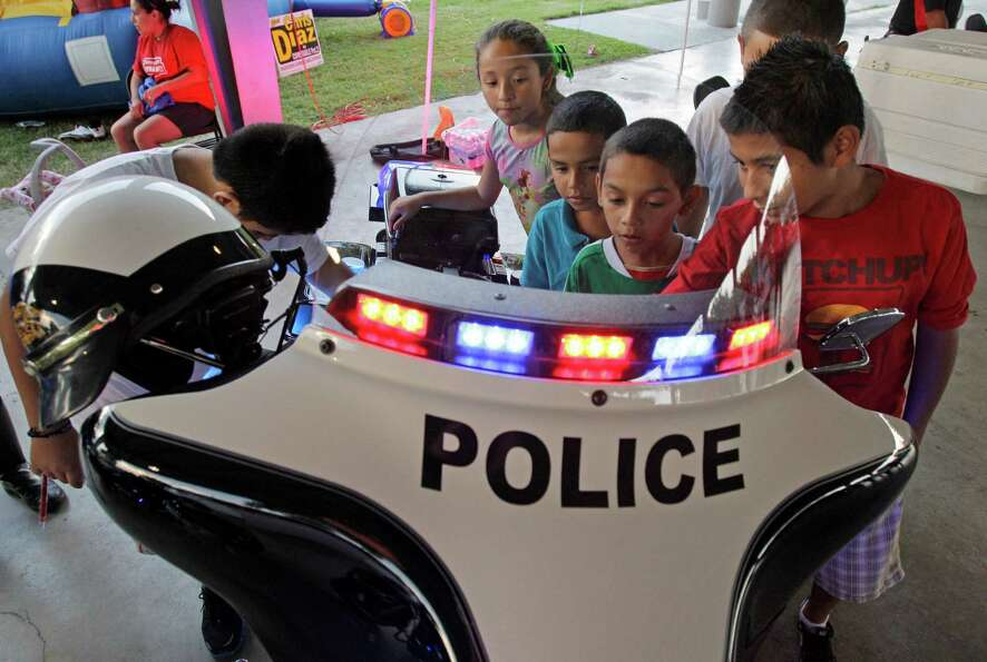 A group of kids look at a South Houston Police Dept. motorcycle during National Night Out at Ave. A
