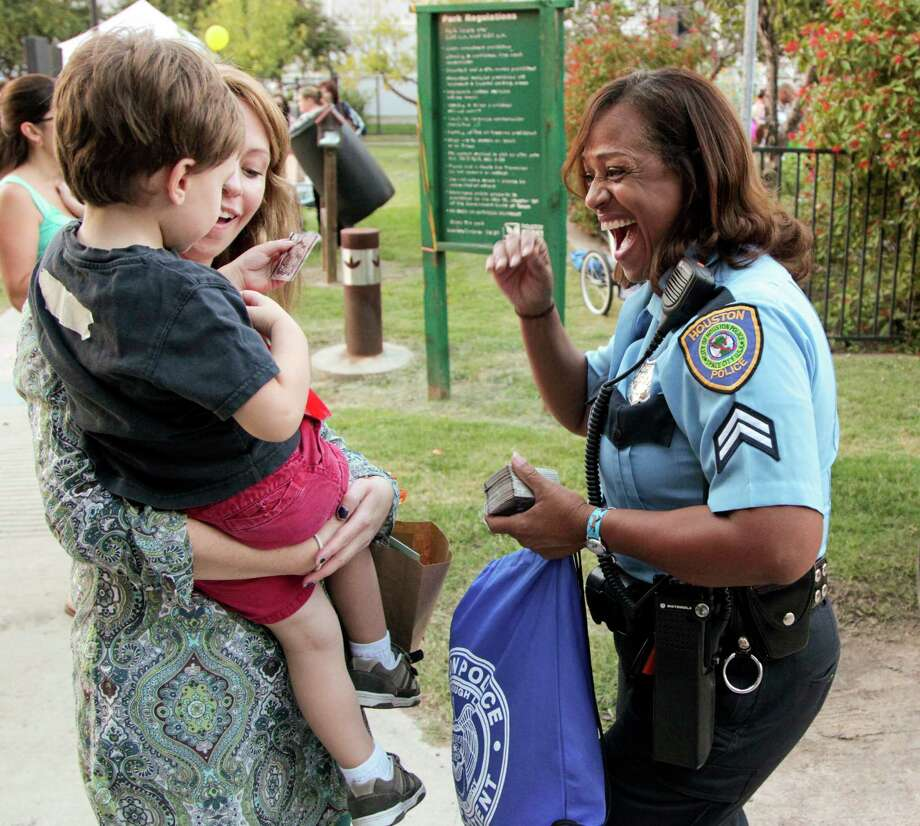 Alejandra Creixell holds her son three year-old Nico Creixell as they meet Senior Police Officer Stephanie Watson-Owens during National Night Out. The event was held at Nellie Keyes Park in the Rice Military neighborhood in Houston, Texas, Tuesday October 2, 2012. Photo: Billy Smith II, Chronicle / © 2012 Houston Chronicle