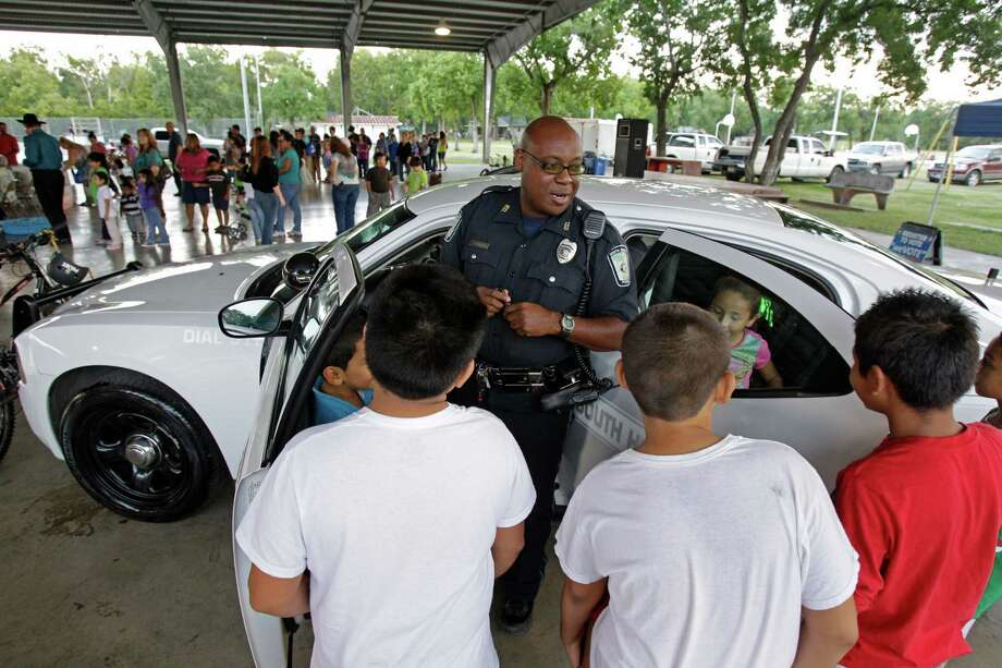 South Houston police officer R. Baxton talks to a group of kids about his police car during National Night Out at Ave. A Park Tuesday, Oct. 2, 2012, in South Houston. Photo: Melissa Phillip, Houston Chronicle / © 2012 Houston Chronicle