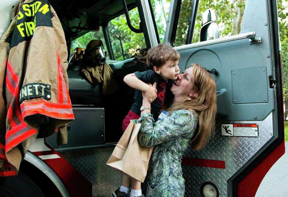Three year-old Nico Creixell is helped out of a fire truck by his mother Alejandra Creixell during National Night Out. The event was held  at Nellie Keyes Park in the Rice Military neighborhood in Houston, Texas, Tuesday October 2, 2012. Photo: Billy Smith II, Chronicle / © 2012 Houston Chronicle
