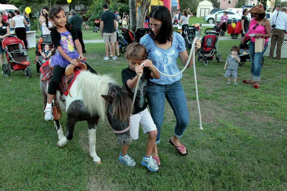 Six year-old Alonbra Fernandez rides a pony as her brother eight year-old Andres Cave and mother Esther Cruz pull her along during National Night Out. Photo: Billy Smith II, Chronicle / © 2012 Houston Chronicle