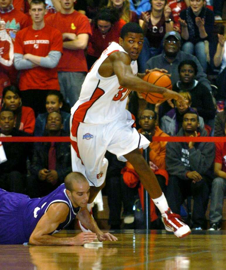 Fairfield University's #30 Shimeek Johnson picks up a loose ball from Holy Cross' #5 Mike Cavataio, during game action at Fairfield University's Alumni Hall in Fairfield, Conn. on Wednesday Dec. 09, 2009. Photo: Christian Abraham / Connecticut Post