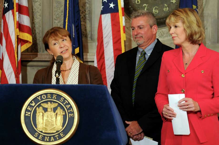 Yancey Migliore of Whitecliff Vineyard in Ulster County, left, speaks on the  Fall in Love with NY Wine campaign to promote state wines during a news conference on Tuesday, Oct. 3, 2012, at the Capitol in Albany, N.Y. Joining her are Tom Edwards, vice president of the NYS Liquor Store Assoc., center, and Sen. Cathy Young. (Cindy Schultz / Times Union) Photo: Cindy Schultz / 00019498A