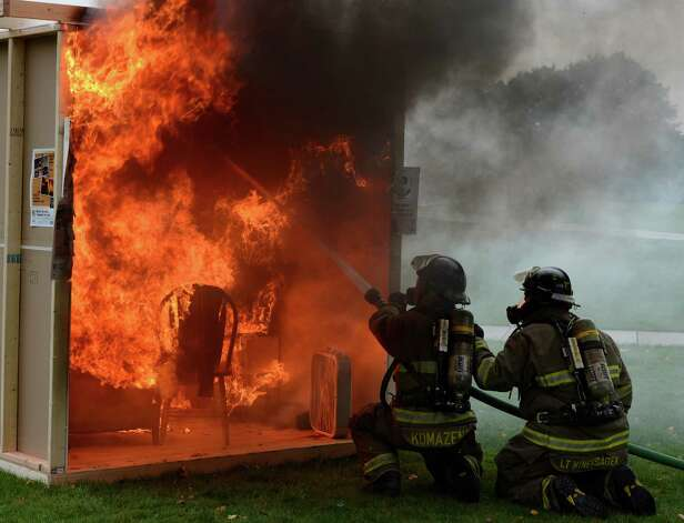 As part of Union College's annual safety day,  a mock dorm room was set afire in Schenectady, N.Y. Oct. 2, 2012.  Schenectady firefighter Mike Komazenski, left and LT. Dan Minersagen extinguished the fire as  Schenectady Fire Department, law enforcement and other agencies joined Campus Safety, Health Services, Emergency Medical Services and other campus groups in providing information on fire and personal safety.    (Skip Dickstein/Times Union) Photo: Skip Dickstein