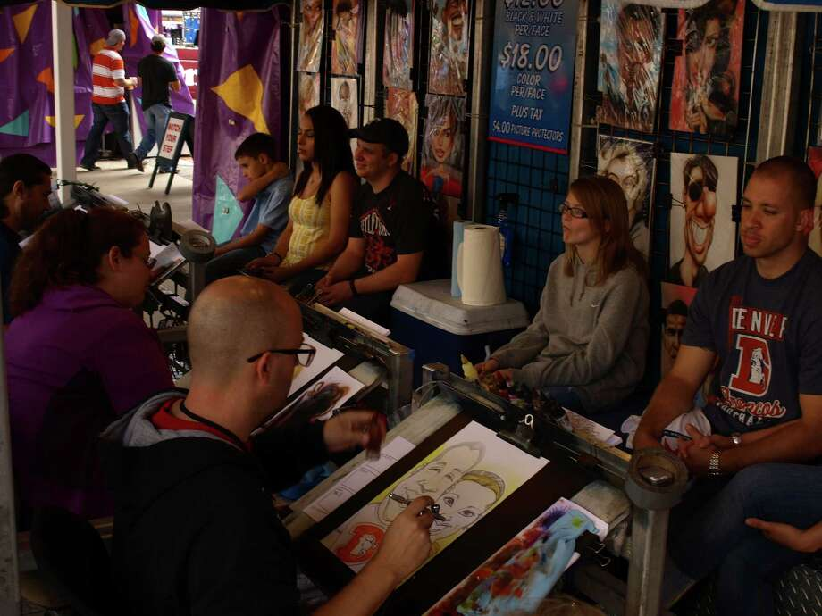 Caricaturists airbrush humorous renditions of fairgoers. Photo: San Antonio Express-News