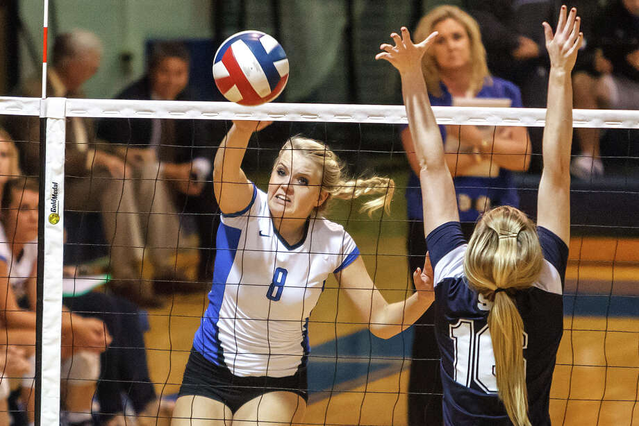 New Braunfels' Morrigan Land (left) sends the ball past Smithson Valley's Allison Meckel during the Unicorns' 25-20, 25-21, 22-25, 25-14 victory at New Braunfels High School. Photo: MARVIN PFEIFFER, San Antonio Express-News / Express-News 2012