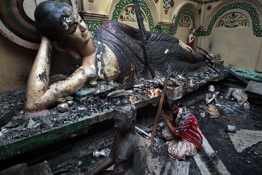 A Bangladeshi Buddhist woman prays in front of a damaged statue at a Buddhist temple which was torched during an overnight attack in Ramu in the coastal district of Cox's Bazar, Bangladesh, Tuesday, Oct. 2, 2012.  About 1,000 Buddhist families fled their villages after rioters burned at least 10 Buddhist temples and 40 homes and looted shops in anger over a Facebook photo of a burned Quran.  Authorities in Bangladesh have ordered security officials to remain alert around official camps of Rohingya Muslims following the attacks. Photo: A.M.Ahad, Associated Press