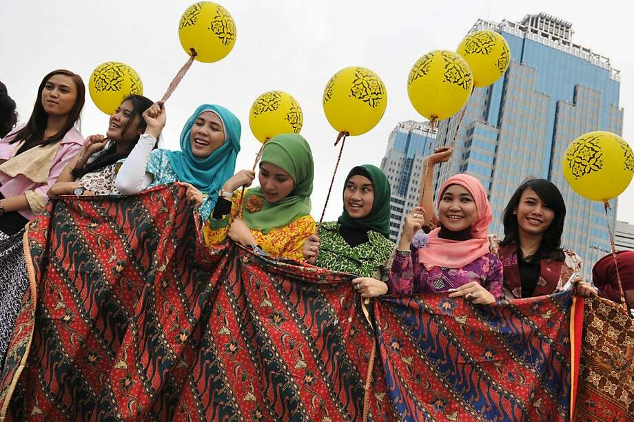 TOPSHOTS  Indonesian employees of Indosat telecom company display various batik designed fabrics during a ceremony marking national batik day in Jakarta on October 2, 2012. Batik's unique wax resistant dyeing technique passed on through generations of artisans and craftsmen creating intricate hand made designed fabric has been recognised by UNESCO as Indonesia's cultural contribution to the world. The craft of batik is intertwined with the cultural identity of the Indonesian people and through the symbolic meanings of its colours and designs, expresses their creativity and spirituality. Photo: Romeo Gacad, AFP/Getty Images