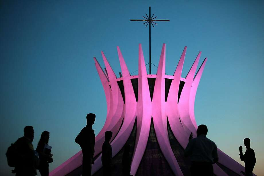 People walk in front of the Cathedral of Brasilia which is illuminated in pink to commemorate breast cancer awareness month in Brasilia, Brazil, Tuesday, Oct. 2, 2012. (AP Photo/Eraldo Peres) Photo: Eraldo Peres, Associated Press