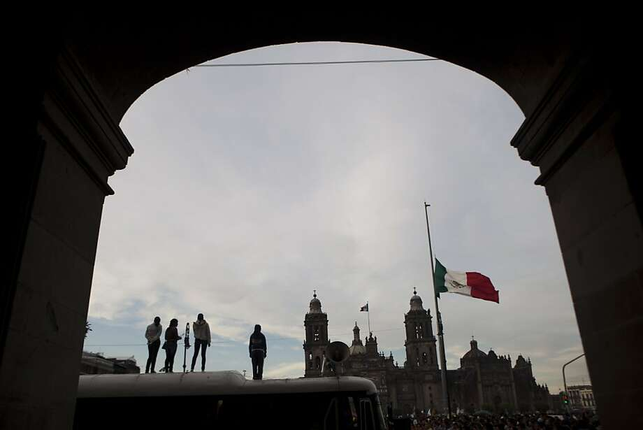 Student stand on the top of a bus during a march marking the 44th anniversary of the Tlatelolco massacre in Mexico City, Tuesday Oct. 2, 2012. On Oct. 2, 1968, soldiers opened fire against a student demonstration in Mexico City's Tlatelolco Plaza just before the capital hosted the Olympics. Official reports said 25 people were killed, but human rights activists say as many as 350 may have died. (AP Photo/Eduardo Verdugo) Photo: Eduardo Verdugo, Associated Press
