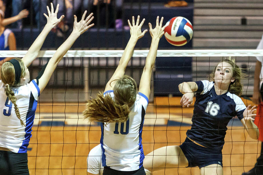 Smithson Valley's Allison Meckel (right) tries to get a shot off past the outstretched arms of New Braunfels' Jessica Waldrip (center) and Neka Cuppettilli during their match at New Braunfels High School on Oct. 2, 2012.  New Braunfels won the match in four sets: 25-19, 25-21, 22-25 and 25-14. Photo: Marvin Pfeiffer, San Antonio Express-News / Express-News 2012