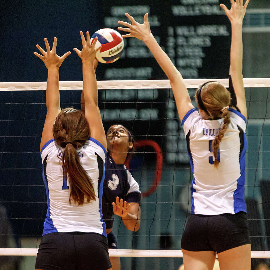 Smithson Valley's Nina Mody-Bailey (center) tries to get a shot past New Braunfels' Cassie Reilly  (left) and Nika Cuppettilli during their match at New Braunfels High School on Oct. 2, 2012.  New Braunfels won the match in four sets: 25-19, 25-21, 22-25 and 25-14. Photo: MARVIN PFEIFFER, Marvin Pfeiffer/ Express-News / Express-News 2012