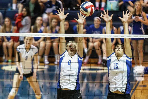 New Braunfels's Morrigan Land (center) and Lauren Kenney go up to block a shot as Neka Cuppettilli looks on during their match with Smithson Valley at New Braunfels High School on Oct. 2, 2012.  New Braunfels won the match in four sets: 25-19, 25-21, 22-25 and 25-14. Photo: Marvin Pfeiffer, San Antonio Express-News / Express-News 2012