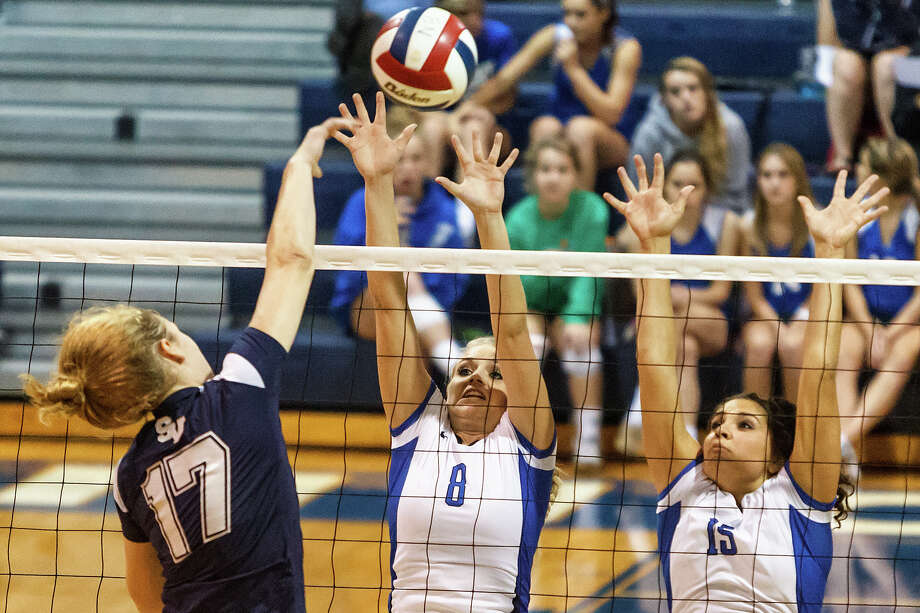 Smithson Valley's McKinlee Boss (left) tries to get a shot past New Braunfels' Morrigan Land (center) and Lauren Kenney during their match at New Braunfels High School on Oct. 2, 2012.  New Braunfels won the match in four sets: 25-19, 25-21, 22-25 and 25-14. Photo: Marvin Pfeiffer, San Antonio Express-News / Express-News 2012