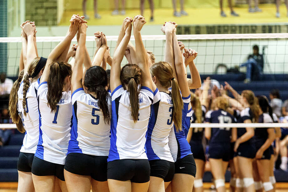 The New Braunfels Lady Unicorns (lef) and Smthson Valley Lady Rangers raise their hands prior to  their match at New Braunfels High School on Oct. 2, 2012.  New Braunfels won the match in four sets: 25-19, 25-21, 22-25 and 25-14. Photo: Marvin Pfeiffer, San Antonio Express-News / Express-News 2012