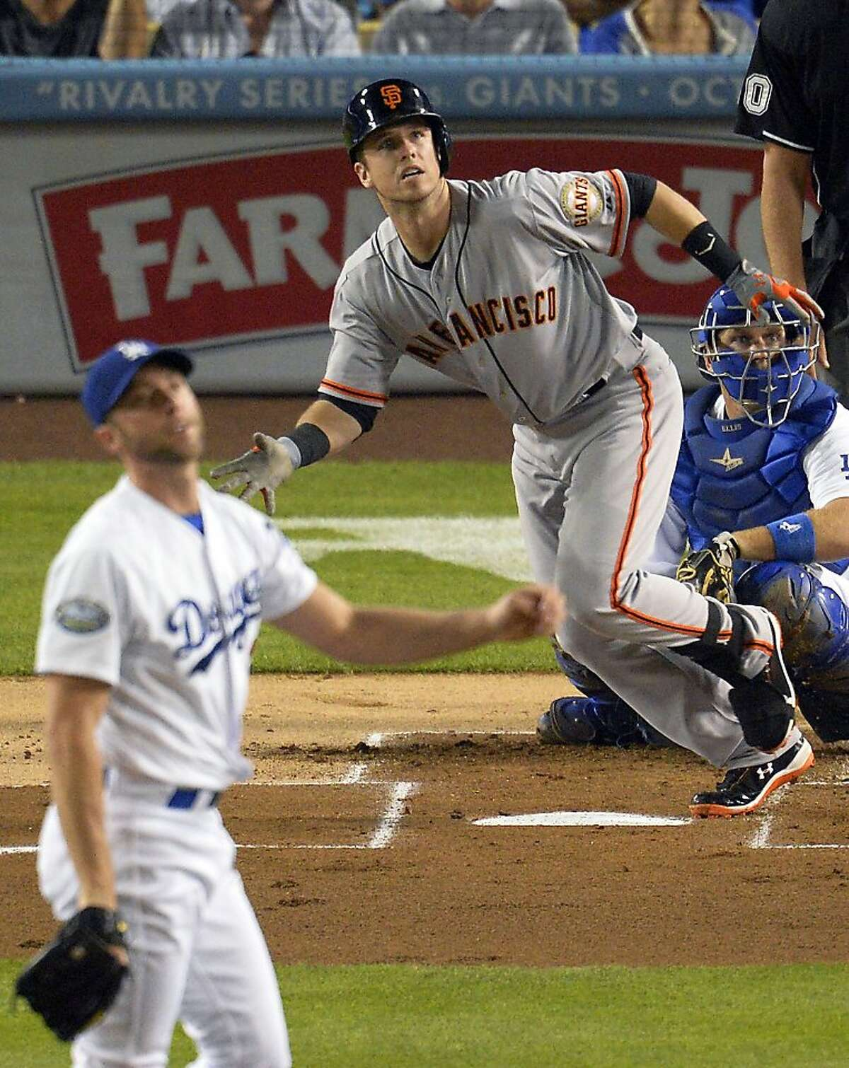 San Francisco Giants' Buster Posey, center, watches his solo home run off Los Angeles Dodgers starting pitcher Chris Capuano, left, during the second inning of a baseball game, Tuesday, Oct. 2, 2012, in Los Angeles. Dodgers catcher A.J. Ellis is at right.