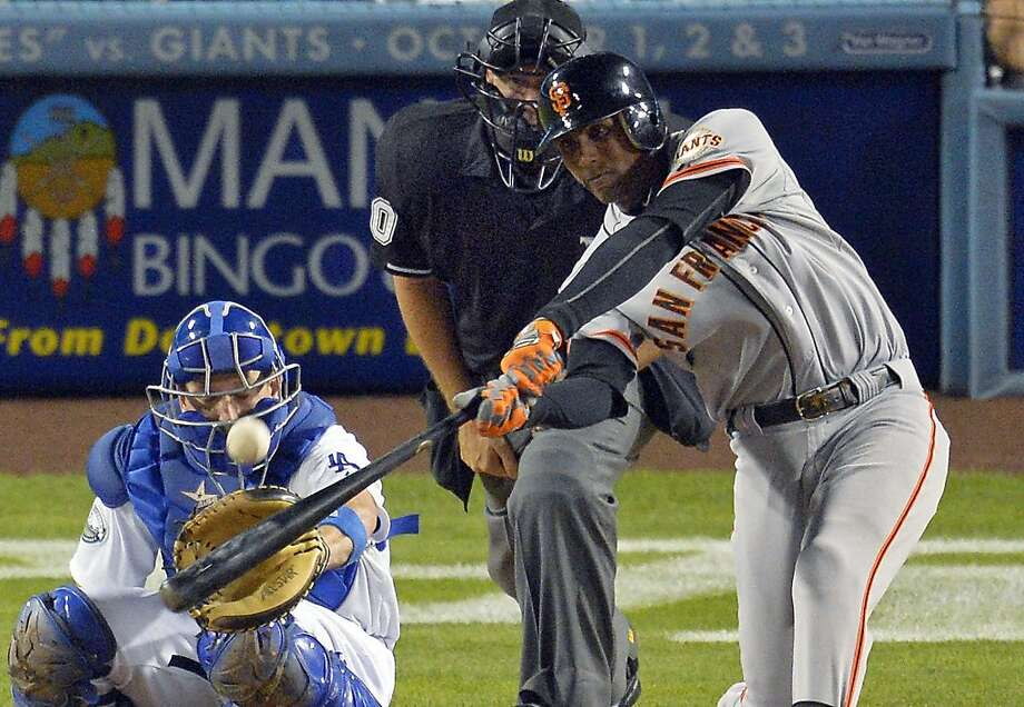 San Francisco Giants' Joaquin Arias hits a solo home run in front of Los Angeles Dodgers catcher A.J. Ellis, left, and home plate umpire Paul Emmel during the third inning of a baseball game Tuesday, Oct. 2, 2012, in Los Angeles. Photo: Mark J. Terrill, Associated Press