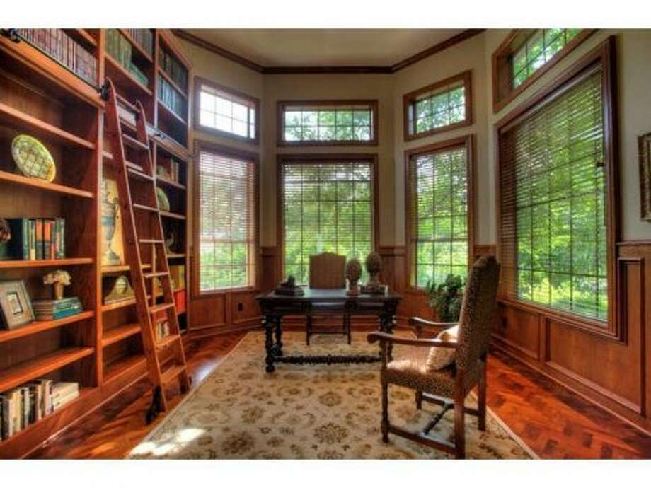 The study contains tall bookcases and a ladder, perfect for housing a personal library.