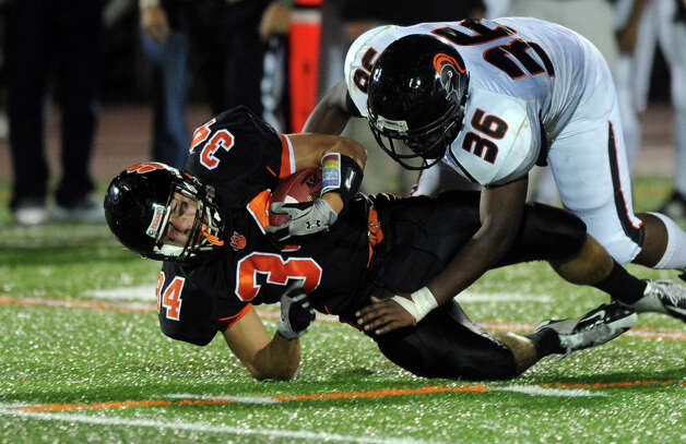 Ridgefield's Will Bonaparte is tackled by Stamford's Ryan Lapotts during Friday's football game at Ridgefield High School on September 28, 2012. Photo: Lindsay Niegelberg / Stamford Advocate