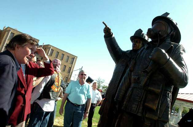 Crowds gather around to admire the bronze sculpture by Ron Petitt during the State of Texas Firefighter Memorial dedication ceremony in front of the Fire Museum of Texas in Beaumont, Saturday. Tammy McKinley/The Enterprise Photo: TAMMY MCKINLEY / Beaumont