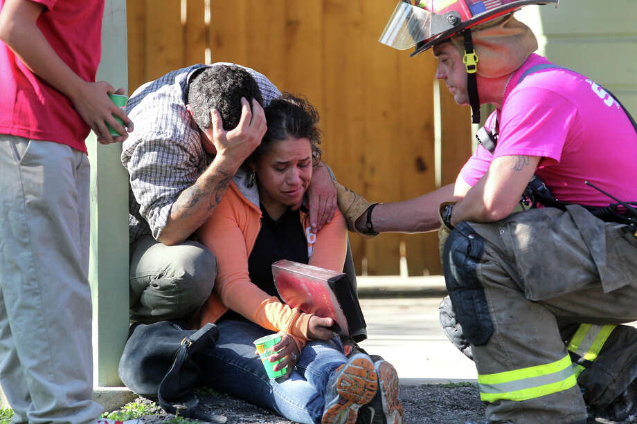 Oct. 3: San Antonio Fire Department fire engineer Jay Cardenas (right) offers comfort after handing over a Bible he found in the debris of the burned residence of Vera Gonzales (center) and Richard Bailey (left). According to SAFD Battalion Chief Armando Perez, Bailey was working on a motorcycle when the fuel ignited and spread into the house destroying the contents of the home and much of the structure. There were no injuries. The couple has three children that also lived at the residence. Read more: Man tips over cycle, burns his home Photo: John Davenport/Express-News
