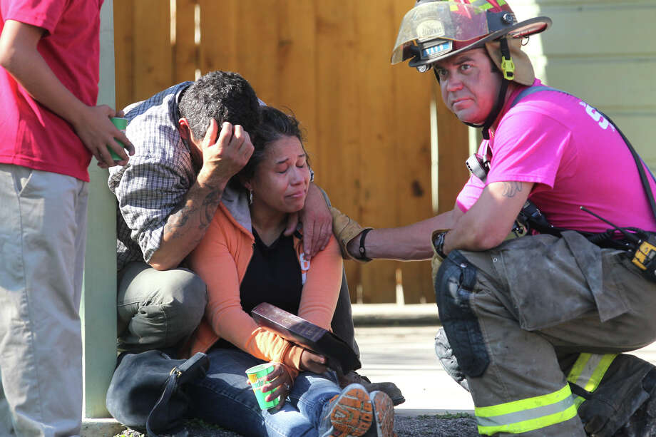 San Antonio Fire Department fire engineer Jay Cardenas (right) looks towards other firefighters after handing over a Bible he found in the debris of the burned residence of Vera Gonzales (eyes closed, holding Bible) and Richard Bailey (left, face covered with hand). According to San Antonio Fire Department Battalion Chief Armando Perez, Bailey was working on a motorcycle at 2702 Wilson #2 about 9:20 a.m. Wednesday October 3, 2012 when the fuel in the motorcycle ignited and spread into Bailey's house destroying the contents of the home and much of the structure. There were no injuries during the incident. The couple has three children that also lived at the residence. Photo: John Davenport/Express-News