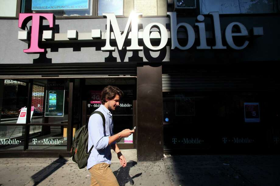 FILE-In this Wednesday, Sept. 12, 2012, file photo  man using a cellphone passes a T-Mobile store, Wednesday, Sept. 12, 2012 in New York. The parent of cellphone company T-Mobile USA on Tuesday, Oct. 1, 2012, said it's in talks to buy smaller MetroPCS Communications Inc., a deal that could shore up two struggling smaller players in the U.S. wireless industry. (AP Photo/Mark Lennihan) Photo: Mark Lennihan / AP