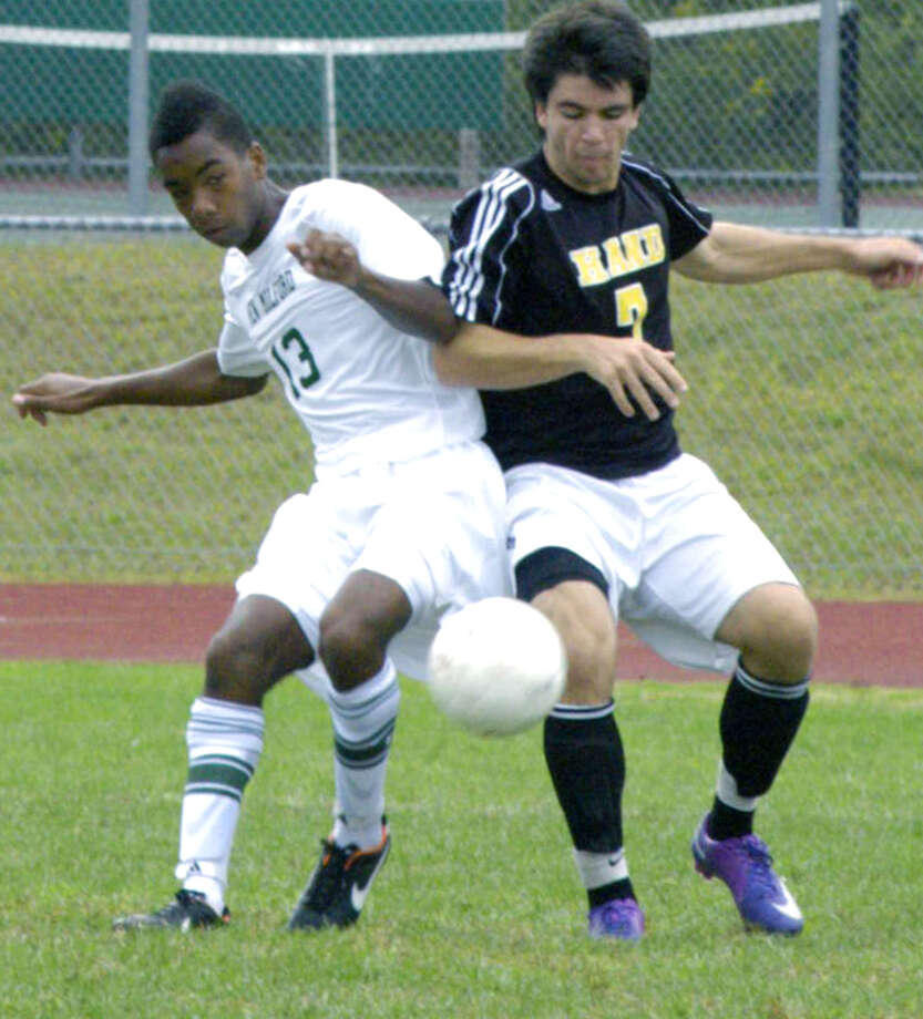 Green Wave co-captain Jaden Wiliams, left, mixes it up with Hand's Gavin Reeves during a spirited match hosted Sept. 22, 2012 by New Milford High School boys' soccer. Photo: Norm Cummings