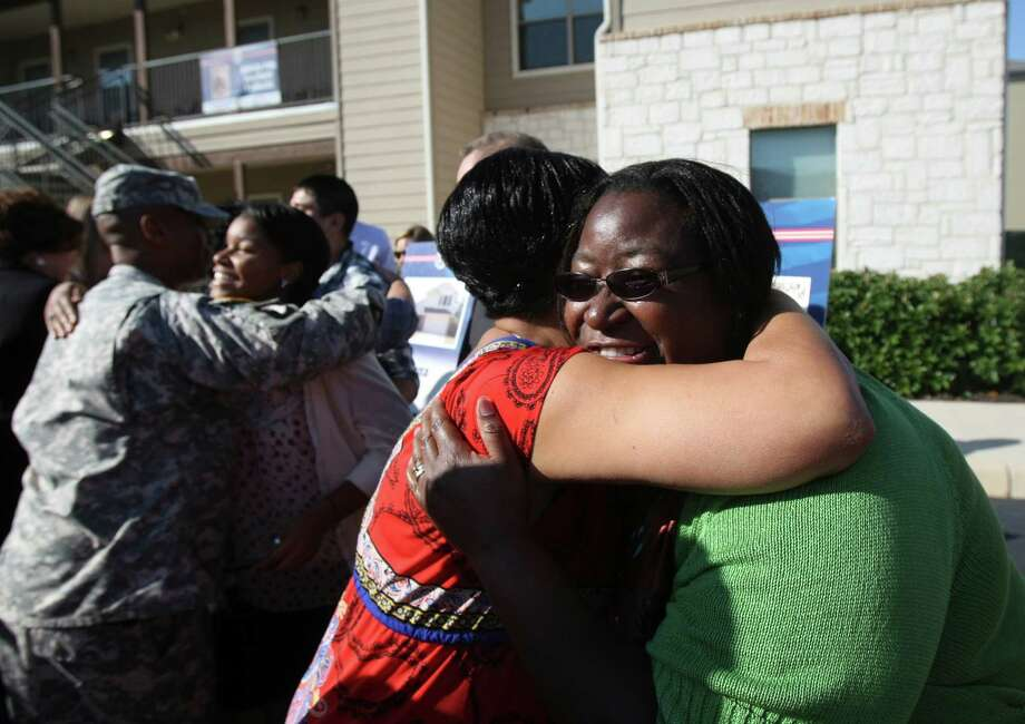 Tanya Crump hugs Mary Dodson after Dodson and her husband and daughter found out they were one of three families awarded mortgage free homes by Operation Homefront and Bank of America on Wednesday Oct. 3, 2012. Photo: Helen L. Montoya, San Antonio Express-News / ©SAN ANTONIO EXPRESS-NEWS