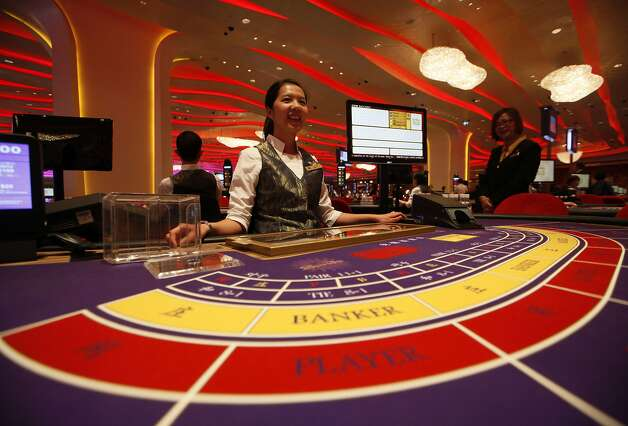 A croupier sits at a baccarat gaming table inside a casino during the opening day of Sheraton Macao Hotel at the Sands Cotai Central in Macau Thursday, Sept. 20, 2012. In the Philippines, a $4-billion casino project will soon rise from reclaimed land on Manila Bay. In South Korea, foreign investors are scheduled to break ground next year on a clutch of casino resorts offshore. The projects are part of a casino building boom rolling across Asia, where governments are trying to develop their tourism markets to capture increasingly affluent Asians with a penchant for gambling.  (AP Photo/Kin Cheung) Photo: Kin Cheung, Associated Press