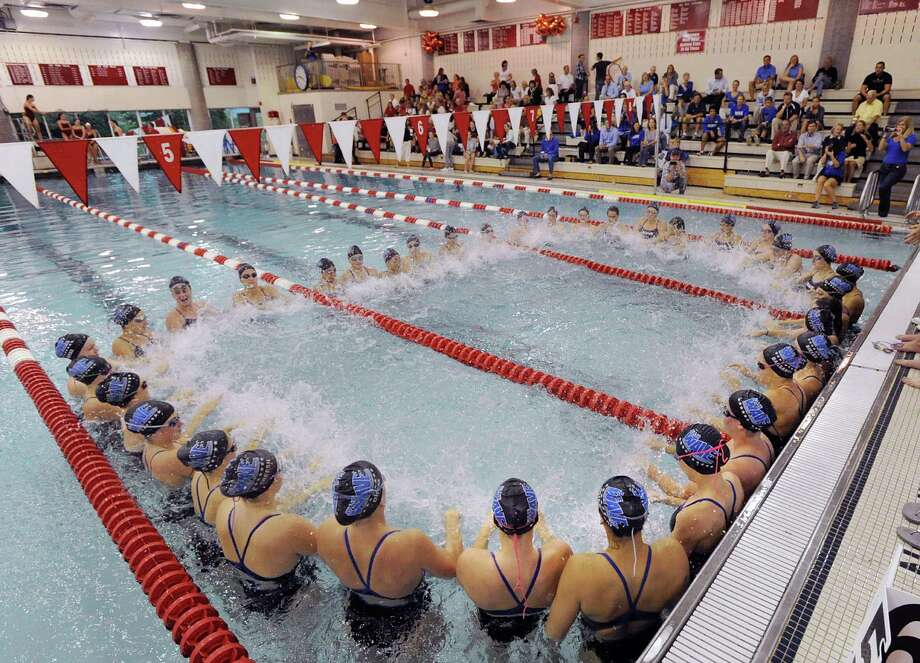 The Darien High School girls swim team does an in-the-pool cheer during the start of the meet against Greenwich High School at Greenwich, Wednesday afternoon, Oct. 3, 2012. Photo: Bob Luckey / Greenwich Time