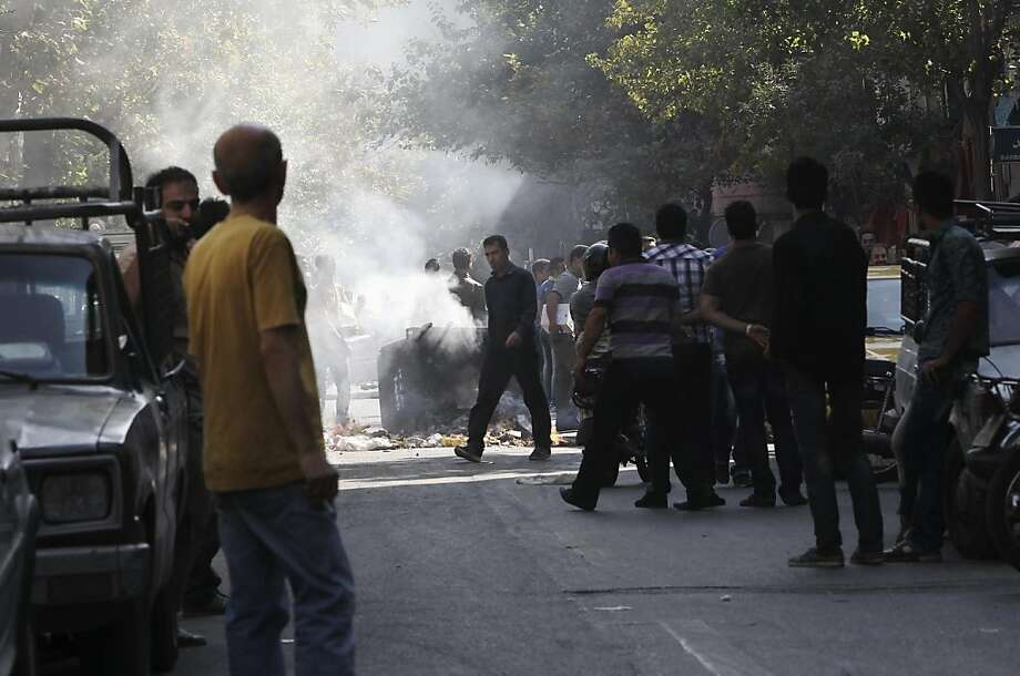 People set a trash can on fire outside Tehran's old main bazaar as the govern-ment took measures to halt the precipitous fall of Iran's currency, threatening those who close their shops and cracking down on money changers. Photo: Anonymous, Associated Press
