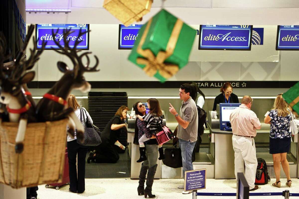 A family check in their luggage as they embark on Thanksgiving holiday travels at Terminal C of Bush Intercontinental Airport Houston, Wednesday, Nov. 23, 2011. ( Michael Paulsen / Houston Chronicle )